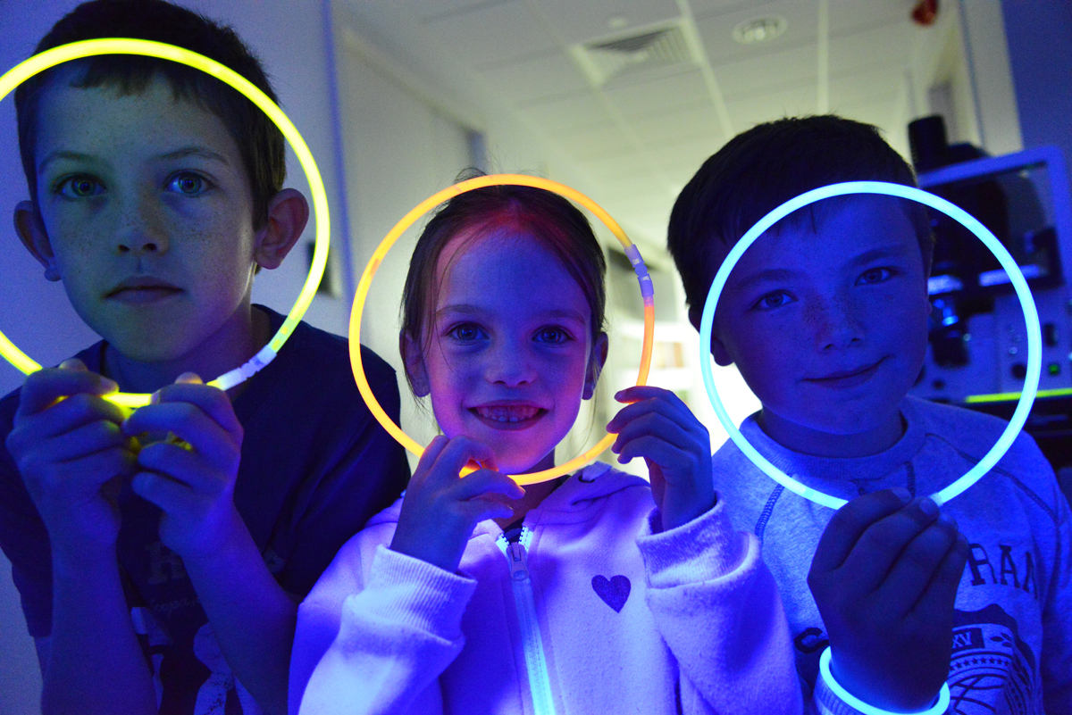 Children holding glow in the dark circles