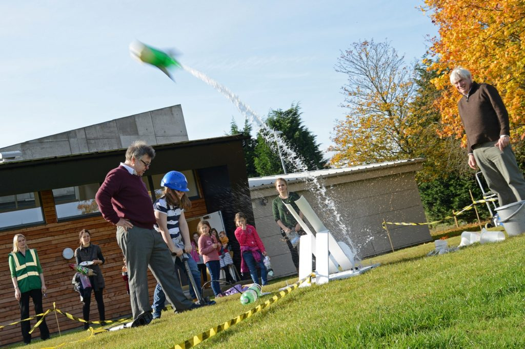 picture of a bottle rocket in mid air, with a trail of water as it blasts off.