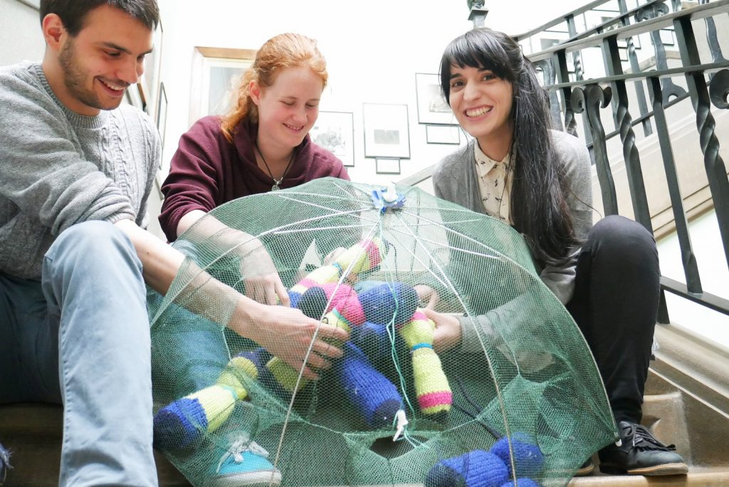 3 people with their hands inside a net, handling coloured objects