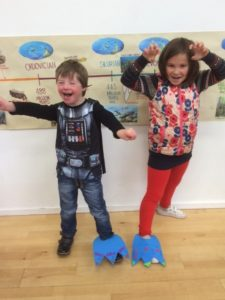 Two Children wearing colourful 'dino feet'