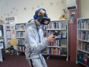Boy in an active standing stance, with a headset with big eye goggles, earphones and holding a black sensor.