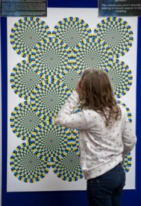 a girl looking at an optical illusion poster with lines and circles